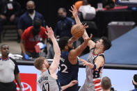 Minnesota Timberwolves center Karl-Anthony Towns (32) loses the ball against Washington Wizards forward Davis Bertans (42) and forward Deni Avdija, right, during the first half of an NBA basketball game, Saturday, Feb. 27, 2021, in Washington. (AP Photo/Nick Wass)