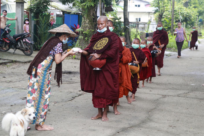 Buddhist monks wearing face mask receive food from devotee as they collect morning alms Thursday, July 15, 2021, in Yangon, Myanmar. (AP Photo/Thein Zaw)