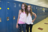 In this Thursday, June 6, 2013 photo, Lyla Vivian, left, and her twin sister, Tessa, one of the twenty-four sets of twins from Highcrest Middle School in Wilmette, Ill., pose for a portrait at the school. The group is attempting to break a Guinness World record for the amount of twins in one grade which is currently 16 sets. (AP Photo/Scott Eisen)