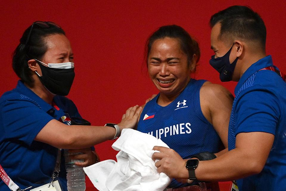 Philippines' Hidilyn Diaz (C) reacts after placing first in the women's 55kg weightlifting competition during the Tokyo 2020 Olympic Games at the Tokyo International Forum in Tokyo on July 26, 2021. (Photo by Vincenzo PINTO / AFP) (Photo by VINCENZO PINTO/AFP via Getty Images)
