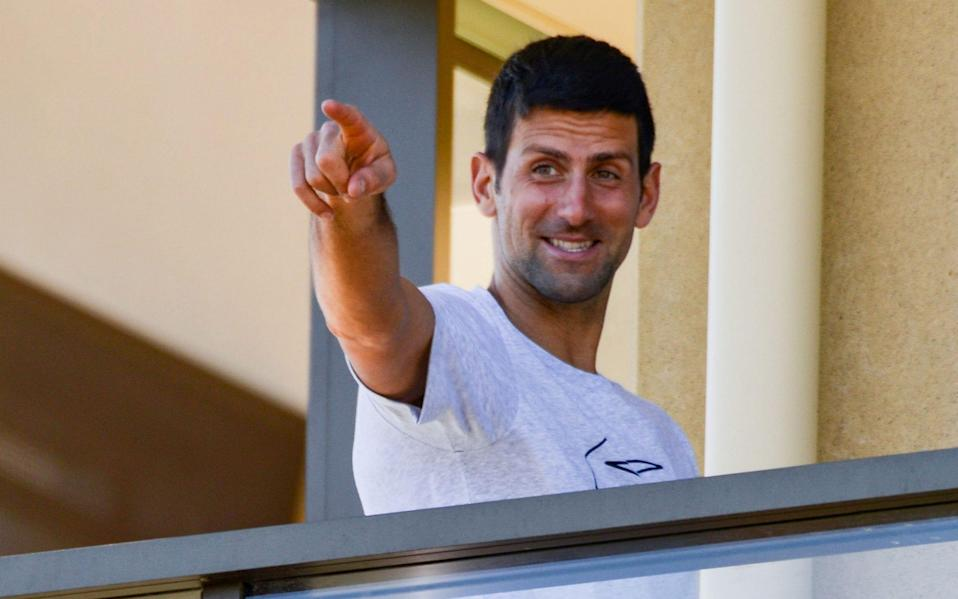 Tennis player Novak Djokovic of Serbia gestures from his hotel balcony in Adelaide - Getty