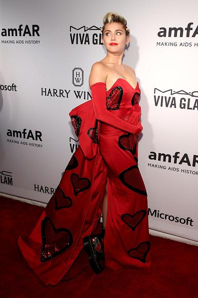 It was her night and she dressed how she wanted to! Miley Cyrus, who was recognized at amfAR's sixth annual Inspiration Gala for her work in the fight against AIDS, wore a custom Moschino gown fittingly covered in Keith Haring-esque hearts. Breaking convention, as per usual, the singer paired her couture dress with Doc Martens made just for her to match. Cyrus, who recently launched the Happy Hippie Foundation, matched her hair with the ensemble with a very punk side braid with red glitter lining her part. As her date, the 22-year-old brought Tyler Ford, a queer, biracial, agender person, whose pronouns are they/them/theirs, who was recently featured on Cyrus' Instagram page, and presented Cyrus with her award. The recent artwork she created of Caitlyn Jenner was also auctioned off to support the charity.