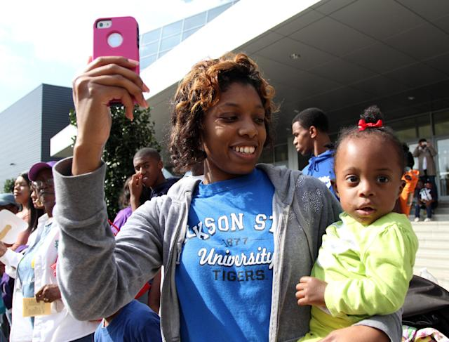 Cristin Ware and her daughter Caitlyn enjoy Jackson State homecoming parade, Saturday, Oct. 19, 2013, in Jackson, Miss. Jackson State decided to continue with homecoming festivities after Saturday's NCAA college football game against Grambling State was canceled because disgruntled Grambling players refused to travel to Jackson. (AP Photo/Charles Smith)