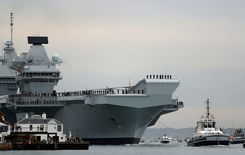 FILE PHOTO: The Royal Navy's new aircraft carrier, HMS Queen Elizabeth, is towed by tugs as it arrives at Portsmouth Naval base, its new home port, in Portsmouth