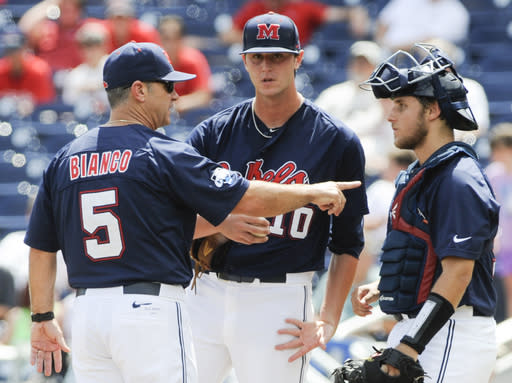 Mississippi coach Mike Bianco (5) talks to pitcher Chris Ellis (10) and catcher Austin Knight, right, in the fourth inning of an NCAA College World Series baseball game against Virginia in Omaha, Neb., Saturday, June 21, 2014. (AP Photo/Eric Francis)