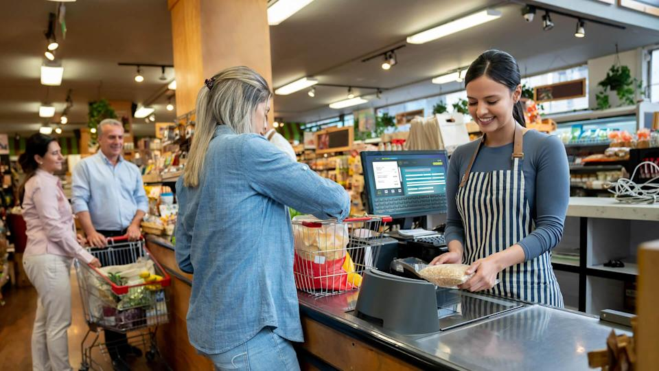 Cheerful employees at supermarket doing checkout for customers  **DESIGN ON SCREEN WAS MADE FROM SCRATCH BY US**.