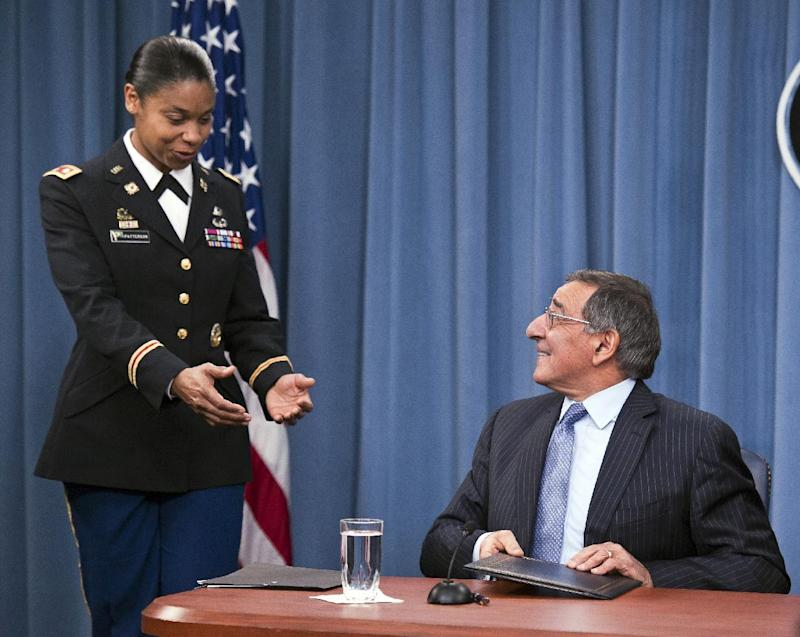 Army Lt. Col. Tamatha Patterson, of Huntingdon, Tenn., waits for Defense Secretary Leon Panetta to hand her the memorandum he has just signed ending the 1994 ban on women serving in combat, Thursday, Jan. 24, 2013,  during a news conference at the Pentagon. (AP Photo/Cliff Owen)