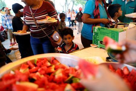 A boy, part of a group of Central American migrants moving in a caravan through Mexico toward the U.S. border, eats watermelon at a shelter set up for the migrants by the Catholic church, in Puebla, Mexico April 6, 2018. REUTERS/Edgard Garrido