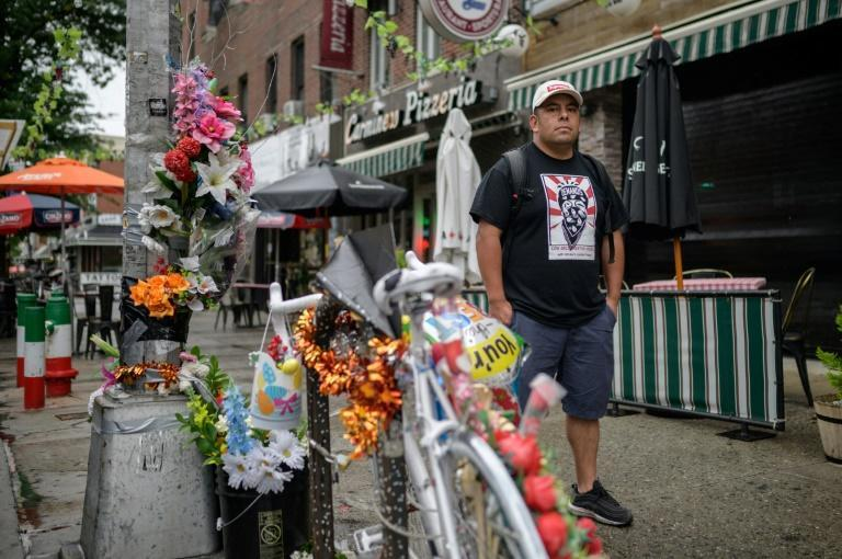 """Gustavo Ajche, one of the founders of """"Los Deliveristas Unidos,"""" poses next to the memorial of a young delivery man who died in a traffic accident with a bus in Brooklyn, New York"""