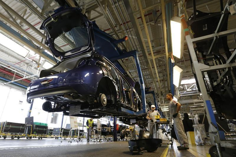 Employees work in the assembly line of the Peugeot 208 at the PSA-Peugeot Citroen plant in Poissy