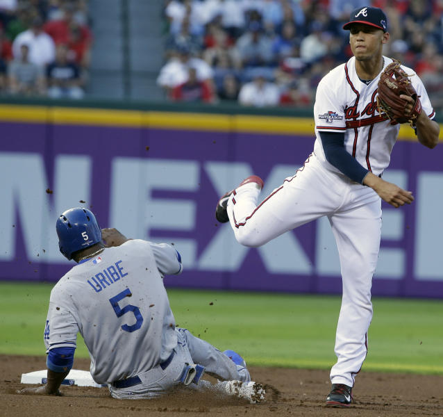 Los Angeles Dodgers Juan Uribe (5) is out at second as Atlanta Braves shortstop Andrelton Simmons, right, throws to first base during Game 2 of the National League division series on Friday, Oct. 4, 2013, in Atlanta. (AP Photo/John Bazemore)