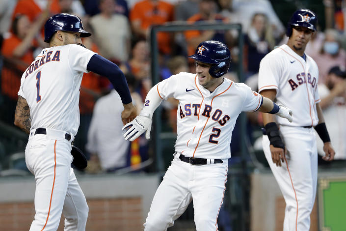 Houston Astros' Carlos Correa (1) and Alex Bregman (2) celebrate as Michael Brantley (23) looks on after they all scored on a three-run home run by Bregman during the third inning of a baseball game against the Los Angeles Angels, Saturday, April 24, 2021, in Houston. (AP Photo/Michael Wyke)