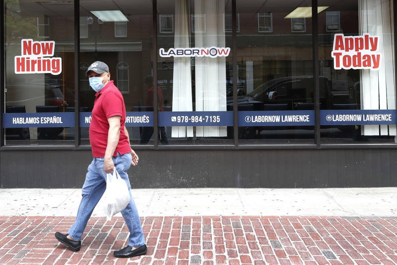 A man walks by a career center storefront, Friday, June 5, 2020, in Lawrence, Mass. The U.S. unemployment rate fell unexpectedly in May to 13.3% — still on par with what the nation witnessed during the Great Depression — as states loosened their coronavirus lockdowns and businesses began recalling workers. (AP Photo/Elise Amendola)