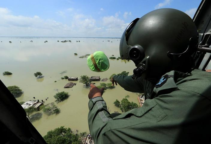 <p>An Indian Air Force official drops relief materials to people affected by floods in Allahabad, India, Wednesday, Aug. 24, 2016. (AP Photo/Rajesh Kumar Singh)</p>