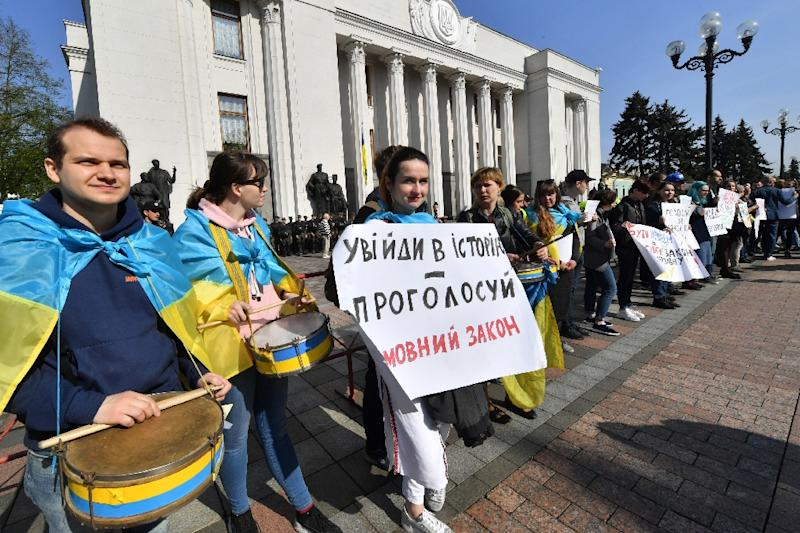 "An activist holds a placard reading ""Become part of the history - vote for the  language law"" during a rally in front of the Ukrainian parliament in Kiev on April 25, 2019"