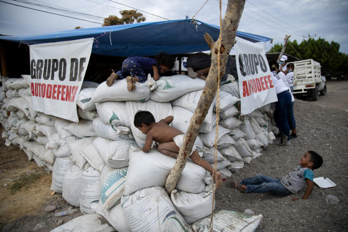 Children play on sandbags at a checkpoint set up by their mothers, who say they are part of a female-led, self-defense group, to protect the entrance of their town of El Terrero in Michoacan state, Mexico, Wednesday, Jan. 13, 2021. Many of the women vigilantes in the hamlet of El Terrero have lost sons, brothers or fathers in the fighting. (AP Photo/Armando Solis)