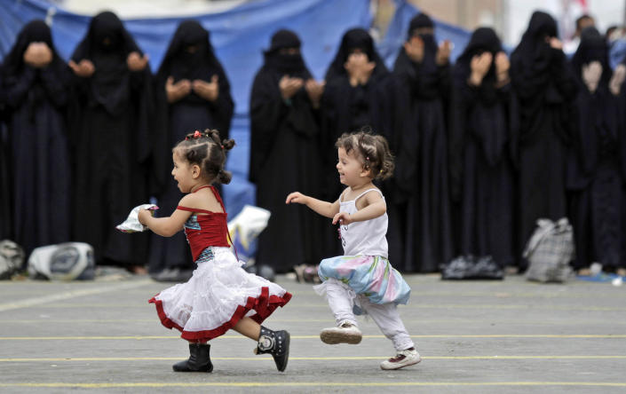 Yemeni girls play in front of female anti-government protestors attending noon prayers, during a demonstration demanding the resignation of Yemeni President Ali Abdullah Saleh, in Sanaa, Yemen, Tuesday, July 5, 2011. Officials in Yemen say airstrikes have killed six militants and three civilians in southern towns seized by Islamist fighters. (AP Photo/Hani Mohammed)