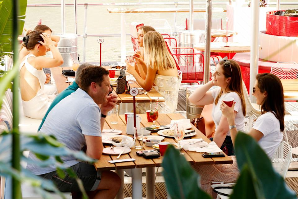 People enjoy outdoor dining along the Yarra River in Melbourne, Australia.