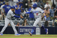Los Angeles Dodgers' AJ Pollock, right, reacts with third base coach Dino Ebel after hitting a two-run home run during the sixteenth inning of a baseball game against the San Diego Padres, Thursday, Aug. 26, 2021, in San Diego. (AP Photo/Gregory Bull)