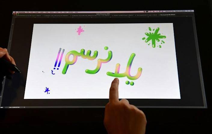 """Artist Reem Ali Adeeb points to the words """"Let's Draw"""" in Arabic script while working in her studio apartment in Los Angeles, California on April 29, 2020, where she is developing online tutorials in Arabic for children about art (AFP Photo/Frederic J. BROWN)"""