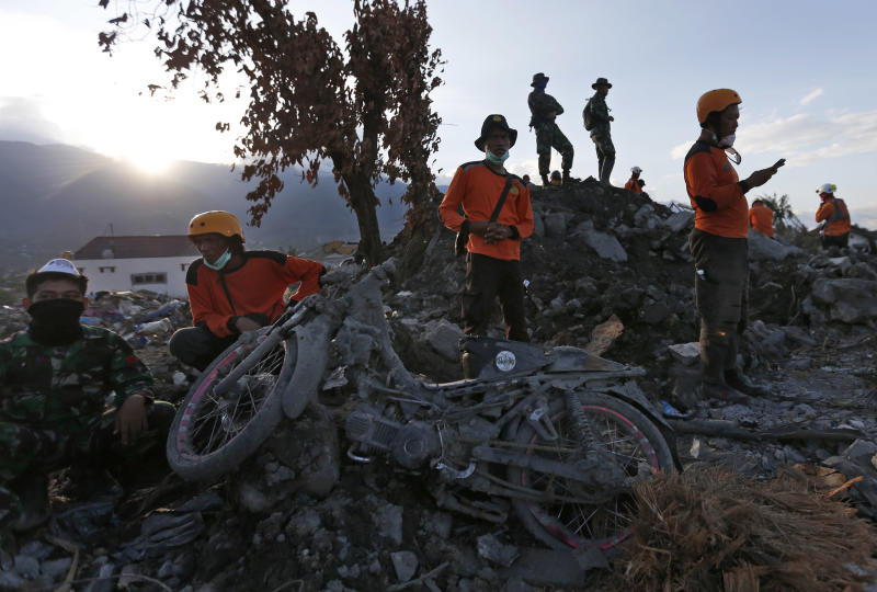 Rescue workers rest during a search for victims of Sept. 28 earthquake at Balaroa neighborhood in Palu, Central Sulawesi, Indonesia, Wednesday, Oct. 10, 2018. Indonesia's disaster agency said Wednesday that it only needs tents, water treatment units, generators and transport from other countries as it responds to the Sulawesi earthquake and tsunami that killed more than 2,000 people. (AP Photo/Dita Alangkara)