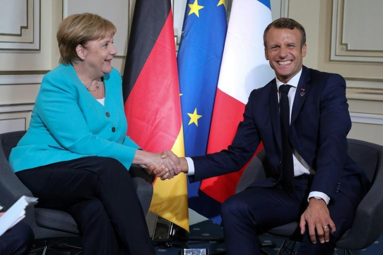 Germany's Chancellor Angela Merkel shares a laugh wih French President Emmanuel Macron (AFP Photo/ludovic MARIN)