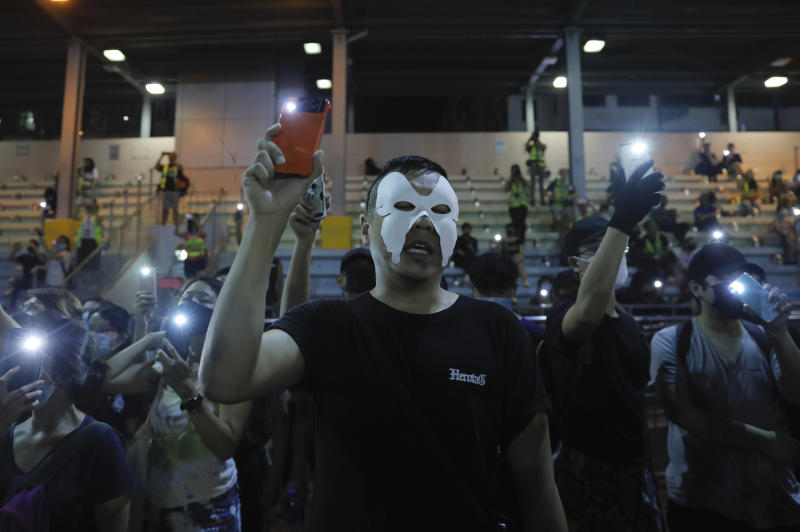 """Masked protesters hold up their lit mobile phones as they sing a protest anthem in Hong Kong on Saturday, Oct. 5, 2019. All subway and train services were suspended, lines formed at the cash machines of shuttered banks, and shops were closed as Hong Kong dusted itself off and then started marching again Saturday after another night of rampaging violence decried as """"a very dark day"""" by the territory's embattled leader. (AP Photo/Kin Cheung)"""