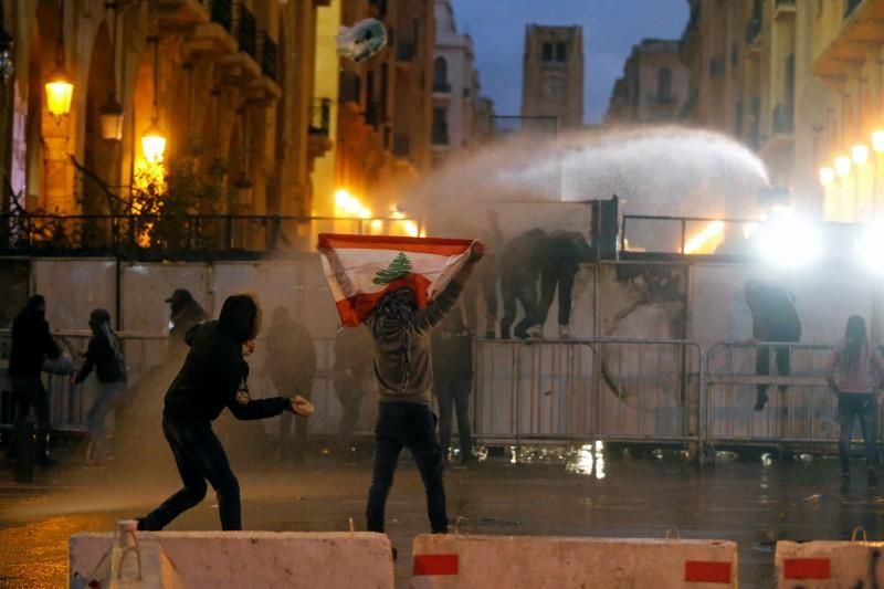 A demonstrator holds up a national flag as police use water cannon during a protest in Beirut