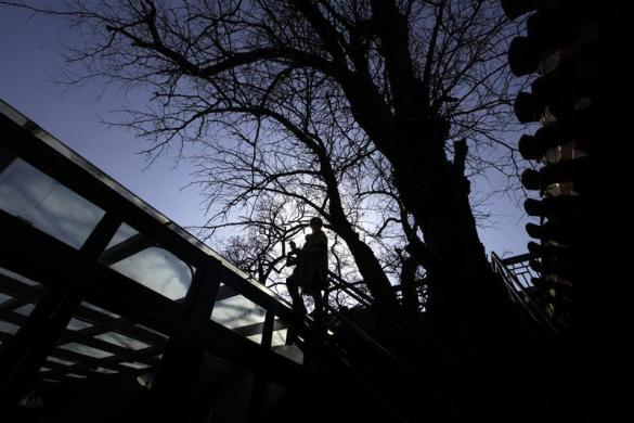 """Ms. Zhuang, a Hotel Test Sleeper, stands on the roof of a public living room of a Beijing traditional hotel with courtyard houses, known as """"Siheyuan"""" in Chinese, in central Beijing March 6, 2012."""