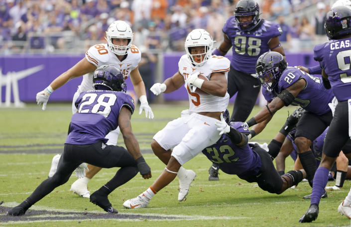 Texas running back Bijan Robinson (5) carries the the ball as a host of TCU defenders close in during the first half of an NCAA college football game Saturday, Oct. 2, 2021, in Fort Worth, Texas. (AP Photo/Ron Jenkins)