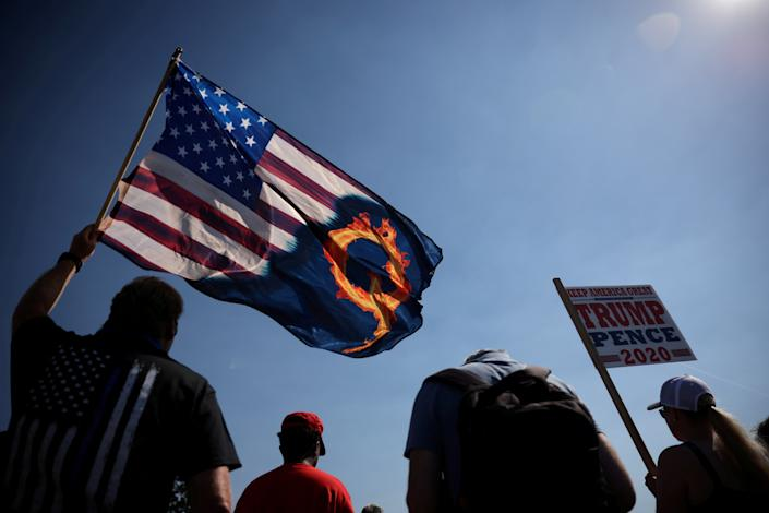 A supporter of President Donald Trump holds an U.S. flag with a reference to QAnon during a Trump 2020 Labor Day cruise rally in honor of Patriot Prayer supporter Aaron J. Danielson, who was shot dead in Portland, Oregon, after street clashes between supporters of President Donald Trump and counter-demonstrators, in Oregon city, Oregon, U.S. September 7, 2020. (Carlos Barria/Reuters)
