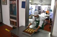 Cook serves food from a kitchen at the First People's Hospital of Xiaoshan Distrinct, Hangzhou