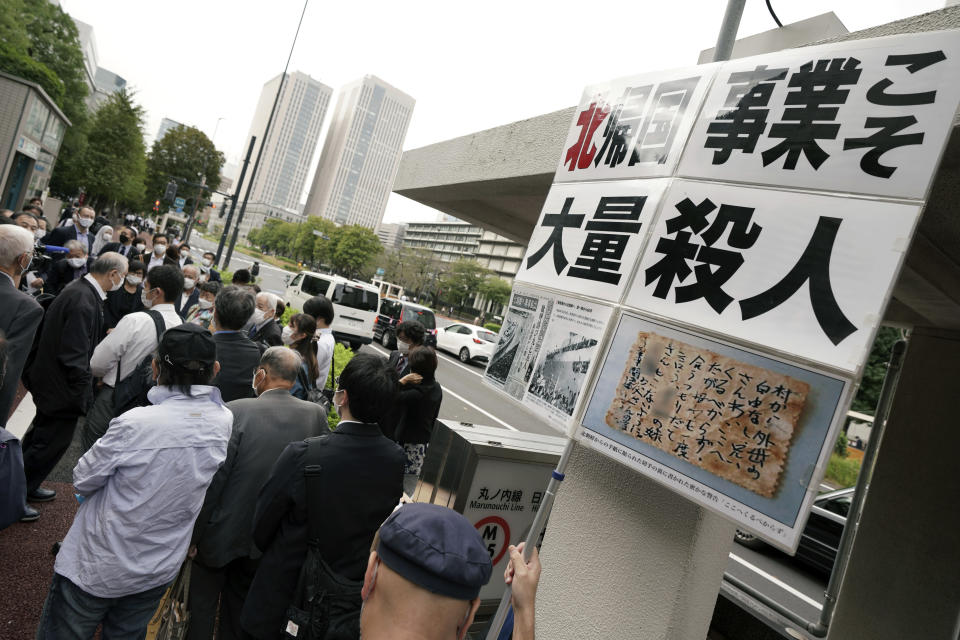 """Plaintiffs and their supporters gather to walk toward the Tokyo District Court Thursday, Oct. 14, 2021, in Tokyo. The court is hearing five ethnic Korean residents of Japan and a Japanese national demanding the North Korean government pay compensation over their human rights abuses in that country after joining a resettlement program there that promised a """"paradise on Earth,"""" but without the presence of a defendant - the North's leader. The banner reads: """"North Korea's 'Paradise on Earth' campaign is mass murder."""" (AP Photo/Eugene Hoshiko)"""