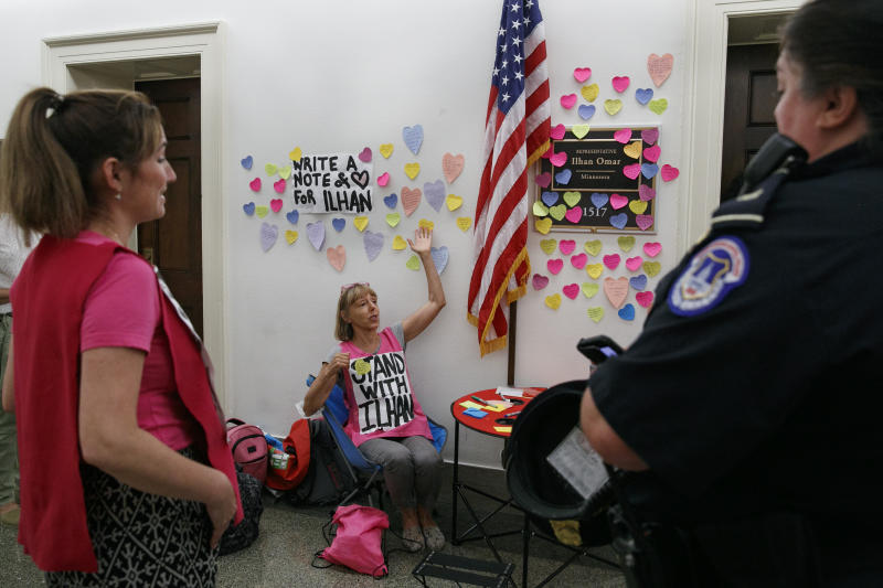 Code Pink co-founder Medea Benjamin, center, gestures as she talks with Capitol Police outside the office of Rep. Ilhan Omar, D-Minn., Friday, July 19, 2019, where heart shaped Post-its line the wall as part of a day-long solidarity vigil organized by the anti-war group, on Capitol Hill in Washington. Capitol Police asked them to remove the chairs and table, and the women complied. (AP Photo/Jacquelyn Martin)
