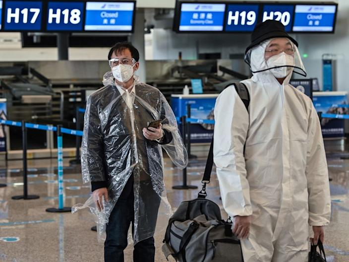 Passengers wearing protective gear walk at Wuhan's Tianhe Airport on April 8, 2020, after its reopening.