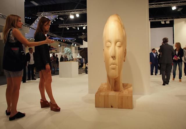 MIAMI BEACH, FL - DECEMBER 05: People look at a piece of art by artist Jaume Plensa in the Galerie Lelong as Art Basel opens at the Miami Beach Convention Center on December 5, 2012 in Miami Beach, Florida. The 11th edition of the art show runs from December 6 through the 9th. (Photo by Joe Raedle/Getty Images)