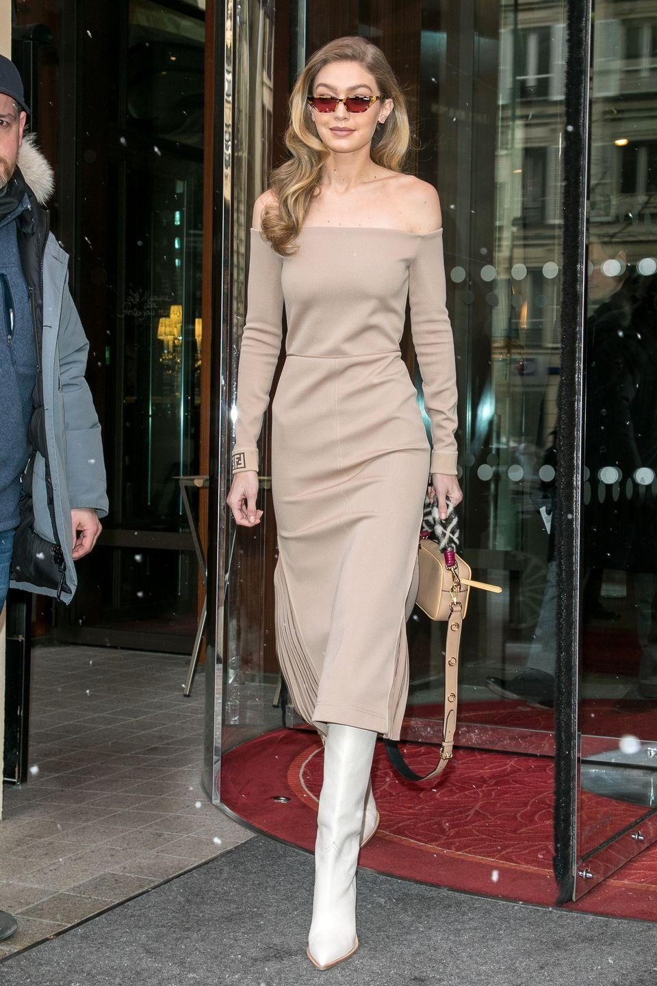 """<p>In a nude off-the-shoulder midi dress, small cat eye tortoiseshell sunglasses from her latest <a href=""""https://www.vogue-eyewear.com/us/gigi-hadid-collection"""" rel=""""nofollow noopener"""" target=""""_blank"""" data-ylk=""""slk:Vogue Eyewear collection"""" class=""""link rapid-noclick-resp"""">Vogue Eyewear collection</a>, a fuzzy-handled <a href=""""https://www.fendi.com/us/woman/new-arrivals?gclid=CjwKCAiAoNTUBRBUEiwAWje2loWOS-NJhGAdv6U9n2LCfSNzTkyYjssWn4qvRhYNpFfz1kTr_2JHOhoCW-gQAvD_BwE"""" rel=""""nofollow noopener"""" target=""""_blank"""" data-ylk=""""slk:Fendi"""" class=""""link rapid-noclick-resp"""">Fendi</a> bag, and white leather pointed-toe <a href=""""https://www.fendi.com/us/woman/new-arrivals?gclid=CjwKCAiAoNTUBRBUEiwAWje2loWOS-NJhGAdv6U9n2LCfSNzTkyYjssWn4qvRhYNpFfz1kTr_2JHOhoCW-gQAvD_BwE"""" rel=""""nofollow noopener"""" target=""""_blank"""" data-ylk=""""slk:Fendi"""" class=""""link rapid-noclick-resp"""">Fendi</a> boots from the Fall 2018 collection while out and about in Paris. </p>"""