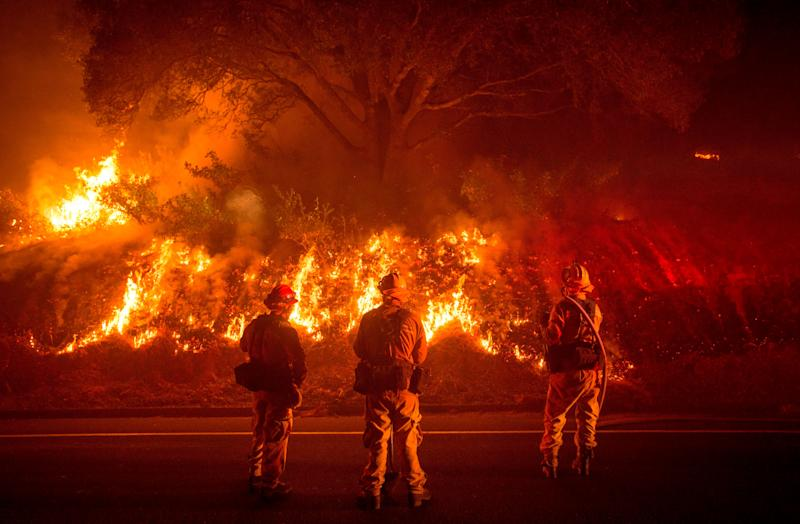 Firefighters monitor flames on the side of a road as the Detwiler fire rages on near the town of Mariposa, California, on July 18, 2017.