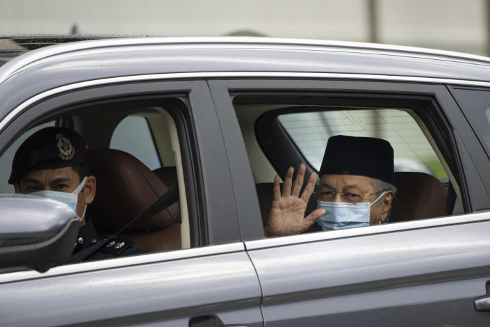 Malaysia's former Prime Minister Mahathir Mohamad, right, wearing a face mask, waves as he leaves National Palace after meeting with the king in Kuala Lumpur, Malaysia, Thursday, June 10, 2021. (AP Photo/Vincent Thian)