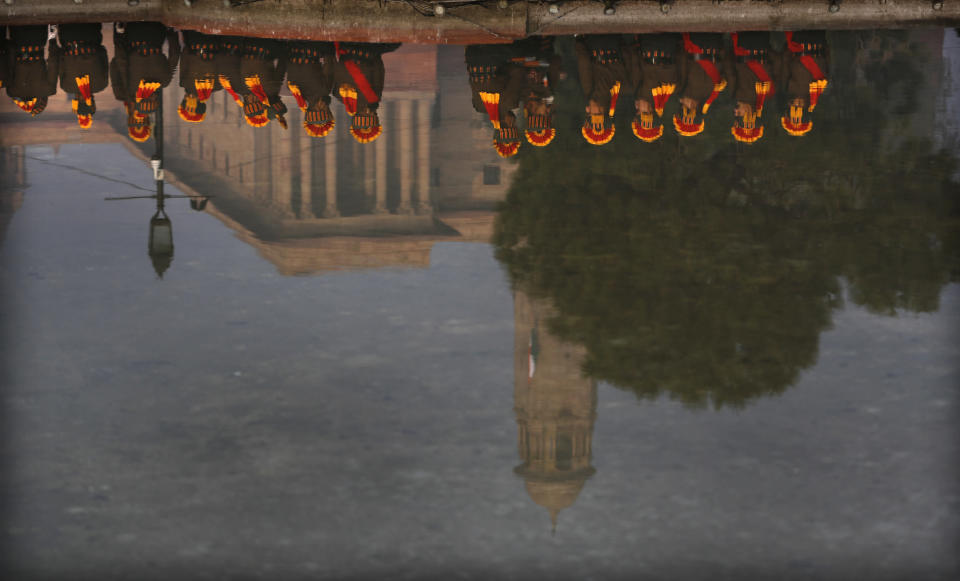 Soldiers are reflected in water from a fountain during rehearsals for the upcoming Republic Day parade in New Delhi, India, Thursday, Jan. 21, 2021. Republic Day marks the anniversary of the adoption of the country's constitution on Jan. 26, 1950. Thousands congregate on Rajpath, a ceremonial boulevard in New Delhi, to watch a flamboyant display of the country's military power and cultural diversity. (AP Photo/Manish Swarup)