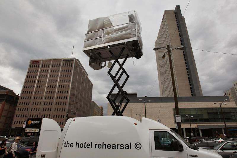 A hotel room made of aluminum and inflated vinyl is held aloft by a van-mounted scissor lift, on promotional display in a parking lot in downtown Denver, Wednesday July 25, 2013. Architectural artist Alex Schweder created the 5 by 7 foot room atop a van for the Biennial of the Americas in Denver. For $50,000, a guest would get one weekend night in the puffy space, plus lots of extras including a diamond pendant and earring set, two iPod Nanos and a dance party for 100 people in a ballroom of The Curtis Hotel. (AP Photo/Brennan Linsley)