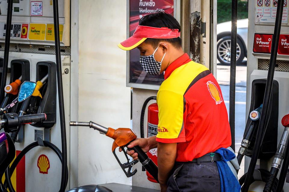 An employee wearing a facemask fills up a car at a gas station in Bangkok on March 9, 2020, as the rapidly spreading coronavirus fans fears over the global economy. (Photo by Mladen ANTONOV / AFP) (Photo by MLADEN ANTONOV/AFP via Getty Images)