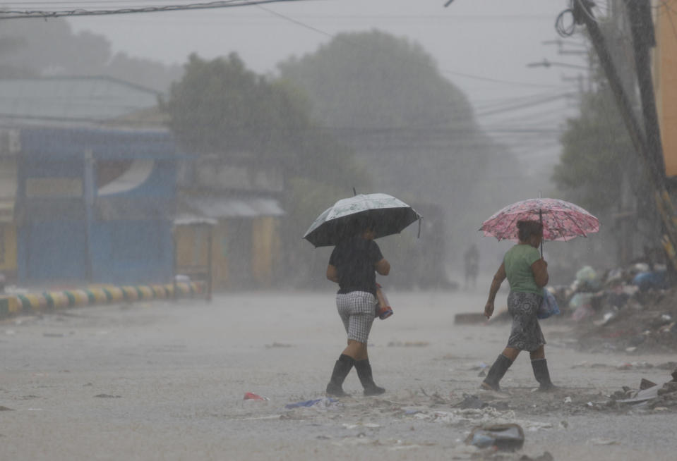Women walk under in the rain brought by Hurricane Iota, in La Lima, Honduras, Tuesday, Nov. 17, 2020. Hurricane Iota tore across Nicaragua on Tuesday, hours after roaring ashore as a Category 4 storm along almost exactly the same stretch of the Caribbean coast that was recently devastated by an equally powerful hurricane. (AP Photo/Delmer Martinez)