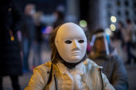 A woman wearing a face mask protests in support of coronavirus deniers and restrictions by the government in downtown Madrid, Spain, Saturday, Nov. 7, 2020. (AP Photo/Manu Fernandez)