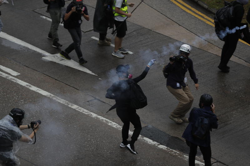 "A protestor throws back teargas shell at police in Hong Kong, Sunday, Oct. 6, 2019. Shouting ""Wearing mask is not a crime,"" tens of thousands of protesters braved the rain Sunday to march in central Hong Kong as a court rejected a second legal attempt to block a mask ban aimed at quashing violence during four months of pro-democracy rallies. (AP Photo/Vincent Thian)"