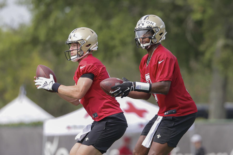 New Orleans Saints quarterback Jameis Winston (2) and quarterback Taysom Hill (7) take snaps during NFL football training camp in Metairie, Friday, July 30, 2021. (AP Photo/Derick Hingle)