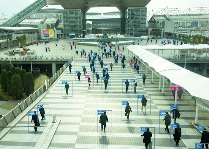 Advanced surveillance software monitors individuals as they walk through an airport terminal.