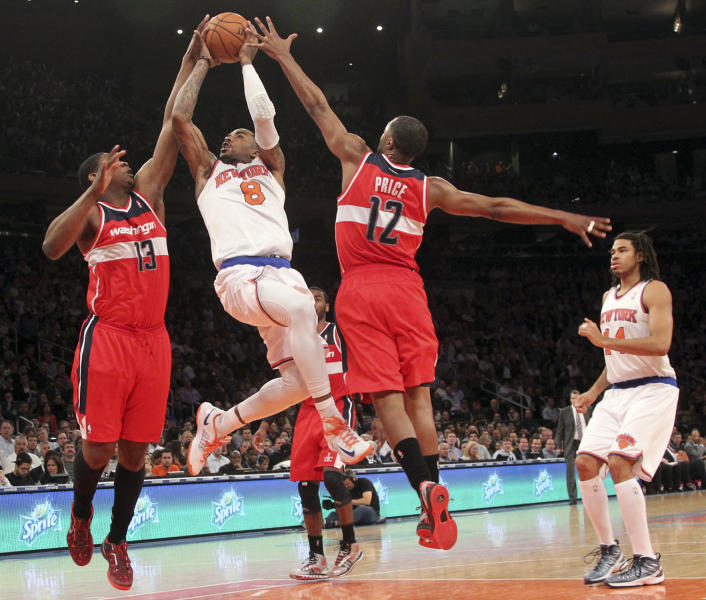 New York Knicks' J.R. Smith goes up past Washington Wizards' Kevin Seraphin (13) and A.J. Price during the second half of an NBA basketball game, Tuesday, April 9, 2013, at Madison Square Garden in New York. The Knicks won 120-99. (AP Photo/Mary Altaffer)