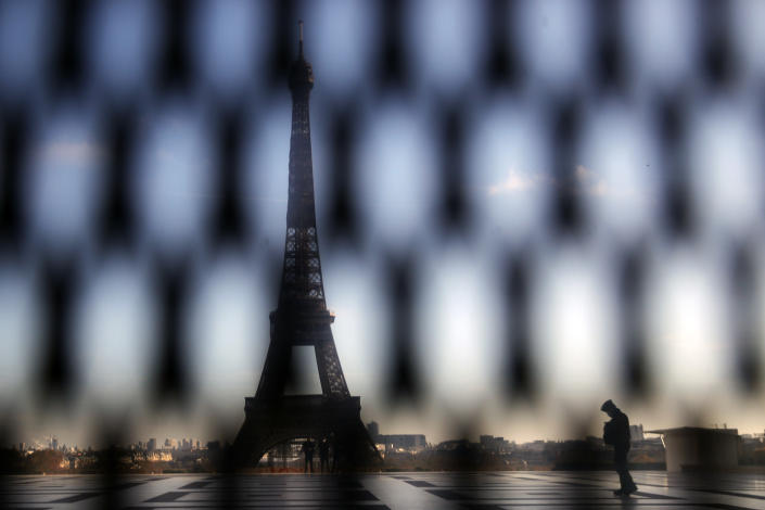 A policeman is pictured through a security fence during a protest against bill on police images, in Paris, Saturday, Nov. 21, 2020. Thousands of people took to the streets in Paris and other French cities Saturday to protest a proposed security law they say would impinge on freedom of information and media rights. The Eiffel tower is seen background. (AP Photo/Christophe Ena)