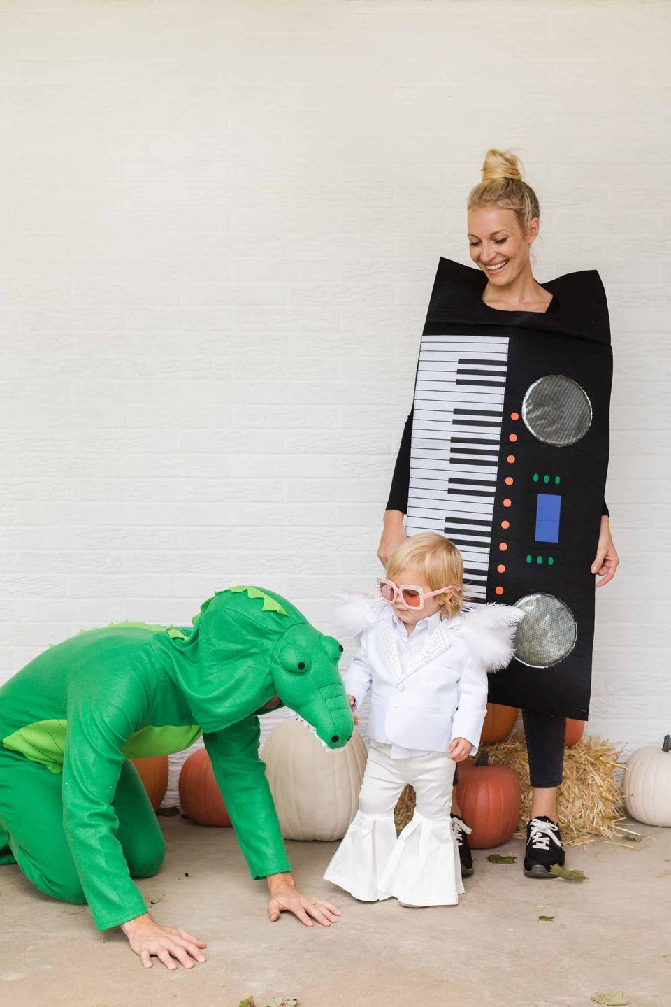 """<p>This adorable family costume brings Elton John's 1972 to hit """"Crocodile Rock"""" to life. </p><p><strong>Find out how it was made at <a href=""""https://abeautifulmess.com/crocodile-rock-family-halloween-costume/"""" rel=""""nofollow noopener"""" target=""""_blank"""" data-ylk=""""slk:A Beautiful Mess"""" class=""""link rapid-noclick-resp"""">A Beautiful Mess</a>. </strong></p><p><strong><a class=""""link rapid-noclick-resp"""" href=""""https://go.redirectingat.com?id=74968X1596630&url=https%3A%2F%2Fwww.walmart.com%2Fip%2FAdult-Piano-Keyboard-Costume%2F108375549%3Firgwc%3D1%26sourceid%3Dimp_xovWUVVskxyOUWEwUx0Mo3bzUkByGTVHqXzVwU0%26veh%3Daff%26wmlspartner%3Dimp_116548%26clickid%3DxovWUVVskxyOUWEwUx0Mo3bzUkByGTVHqXzVwU0%26affiliates_ad_id%3D565706%26campaign_id%3D9383&sref=https%3A%2F%2Fwww.countryliving.com%2Fdiy-crafts%2Fg22500148%2F70s-costumes%2F"""" rel=""""nofollow noopener"""" target=""""_blank"""" data-ylk=""""slk:SHOP KEYBOARD COSTUME"""">SHOP KEYBOARD COSTUME</a><br></strong></p>"""